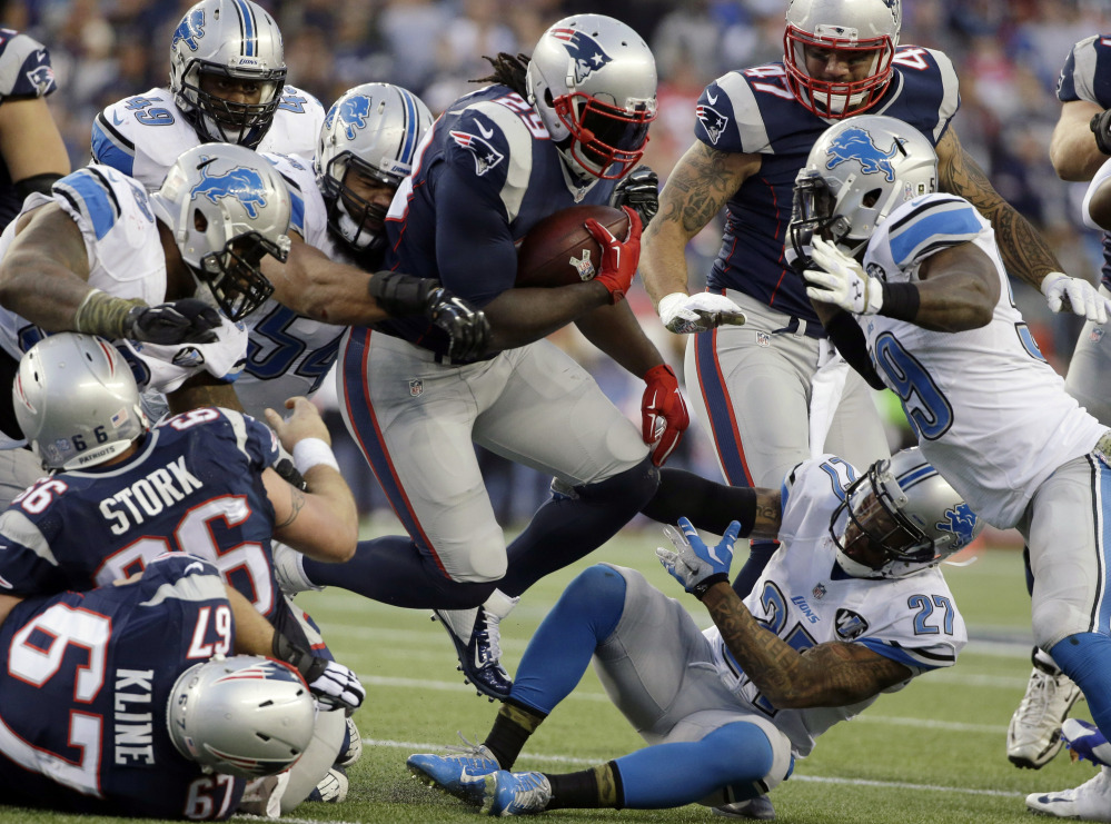 New England Patriots running back LeGarrette Blount, center, runs over Detroit Lions free safety Glover Quin (27) in the second half Sunday in Foxborough, Mass. Blount scored two touchdowns and the Patriots won 34-9.