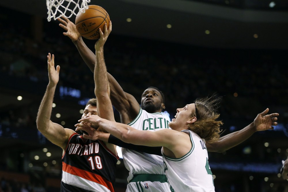 Portland Trail Blazers' Joel Freeland (19) battles Boston Celtics' Jeff Green, center, and Kelly Olynyk for the rebound in the fourth quarter Sunday. The Portland Trail Blazers won 94-88.