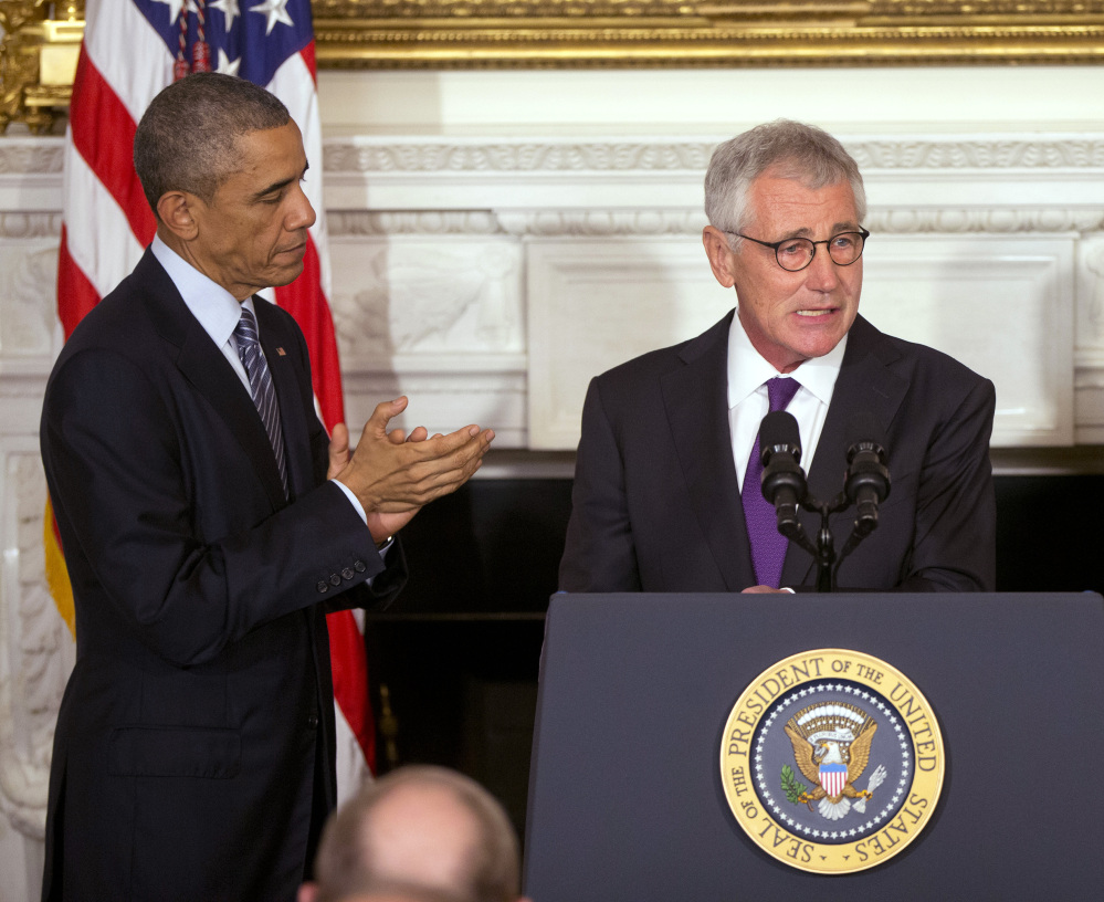 President Obama applauds Defense Secretary Chuck Hagel at the White House on Monday as Hagel's resignation is announced. Hagel is stepping down under pressure after struggling to break through the White House's insular foreign policy team.