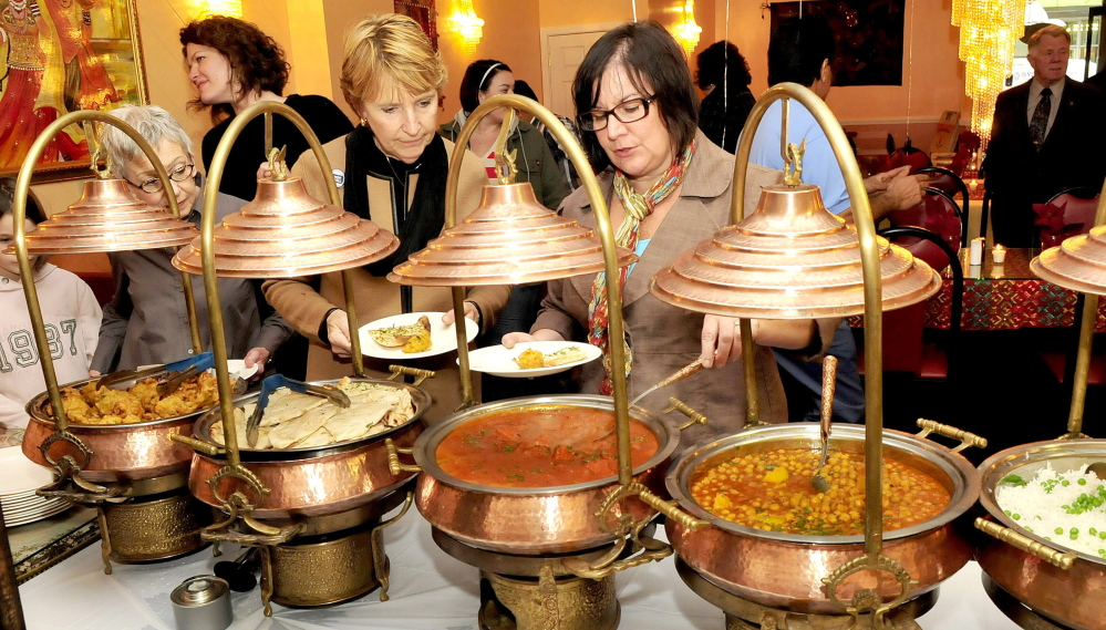 Staff photo by David Leaming June L'Heureux, left, and Jennifer Olsen of the Waterville Main Street organization sample dishes served during an opening at the Jewel of India restaurant in Waterville on Monday. Local business leaders say the addition of a  restaurant featuring Indian cusine helps to fill out the menu choices available in the city, and help make Waterville a destination spot for people in central Maine.