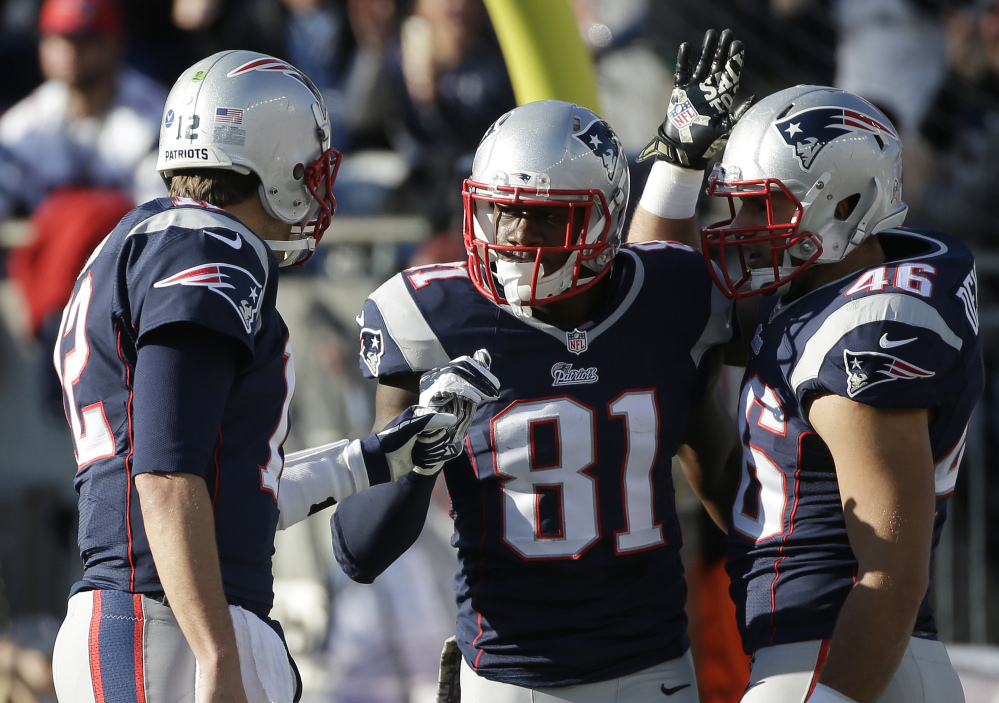 New England Patriots quarterback Tom Brady, left, celebrates his touchdown pass to New England Patriots tight end Timothy Wright (81) in the first half Sunday against the Detroit Lions in Foxborough, Mass. The Patriots won 34-9.