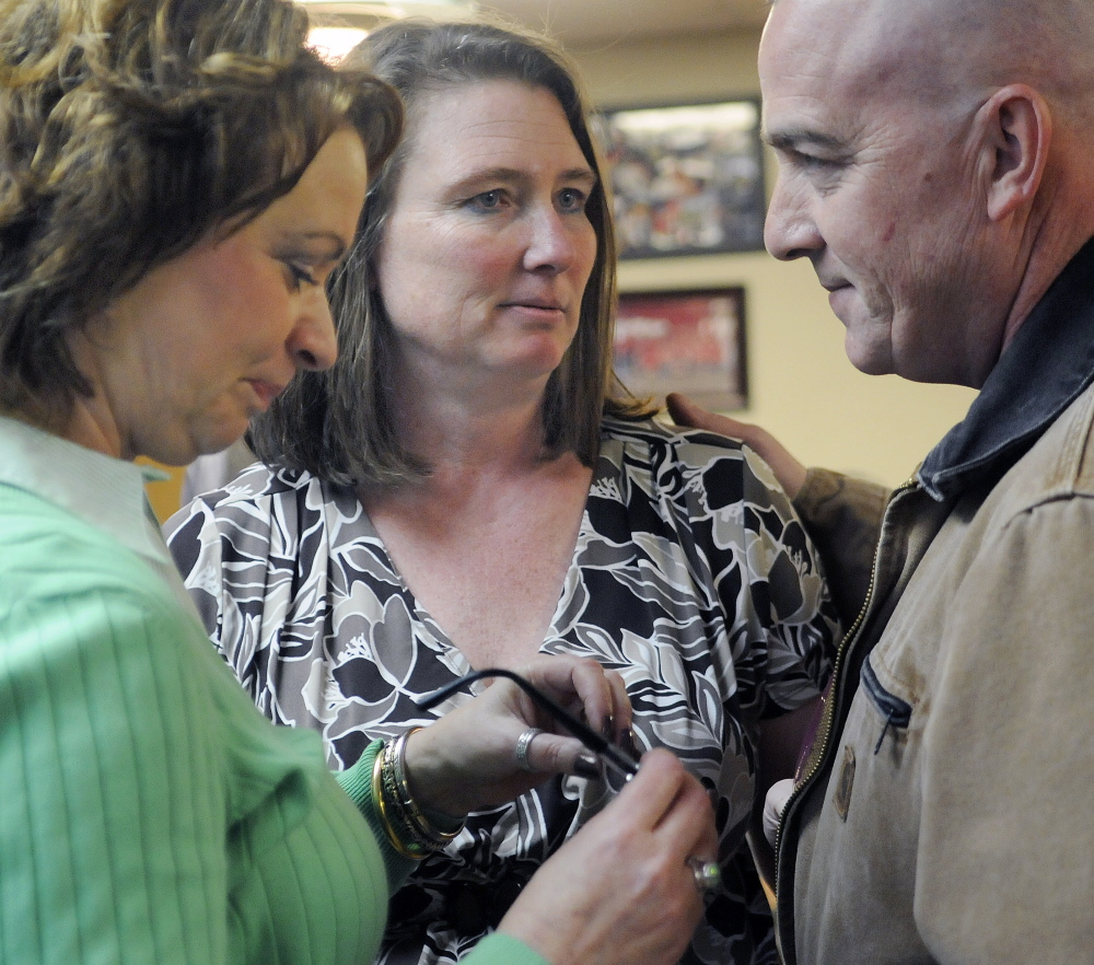 Randi Taylor, left, and her husband, Scott, speak Monday with Cathy Gregoire at the Red Barn during a fundraiser for her husband, Robert Gregoire, the Augusta police chief. The chief was severely injured in a September motorcycle accident, and the community rallied at the Augusta restaurant to raise funds to purchase adaptive equipment for him. Scott Taylor is an Augusta Police Officer who has served with Gregoire for several years.