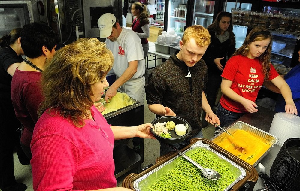 Volunteers load up turkey dinners on plates for the 2013 community Thanksgiving dinner at The Red Barn restaurant in Augusta. The menu included turkey, stuffing, potatoes, peas and squash.