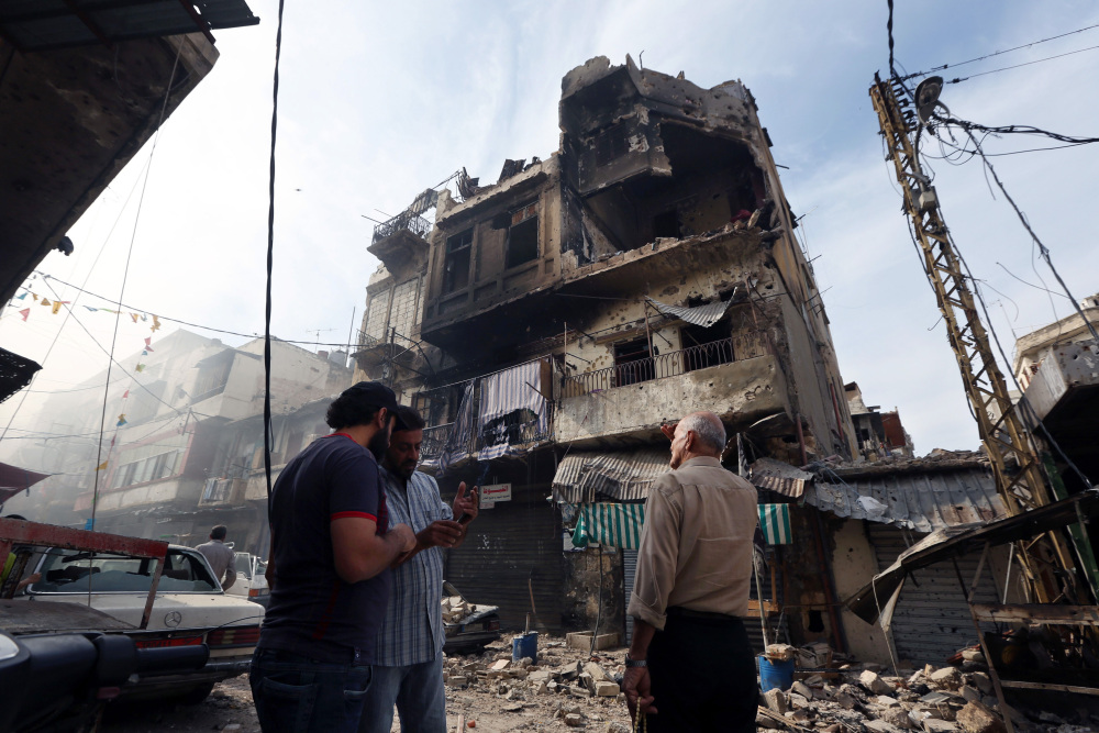 In this Oct. 27, 2014, file photo, Lebanese men stand near buildings damaged due to clashes between the Lebanese army and Islamic militants in the northern port city of Tripoli, Lebanon.
