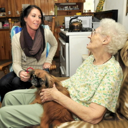 Ashley Conners, left, regional nutrition assistant with the Meals on Wheels program, speaks with recipient Eurline Perkins at her home in Skowhegan on Tuesday.