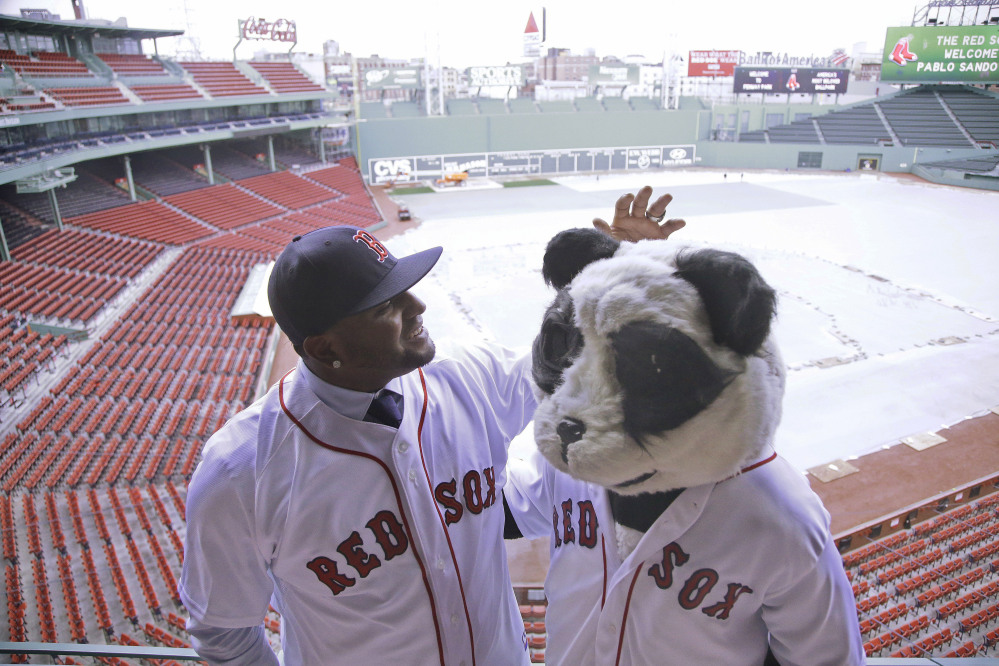 Newly acquired Boston Red Sox free agent third baseman Pablo Sandoval, nicknamed Kung Fu Panda, converses with a person dressed as a panda bear wearing a Red Sox jersey, overlooking a snow covered  Fenway Park field Tuesday in Boston.
