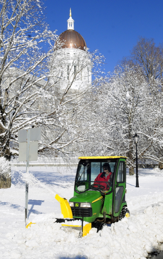 Richard Lachance Jr. runs a tractor with a snowblower along sidewalk in front the State House on Thursday after an overnight snowstorm in Augusta. He and other Bureau of General Services workers spent their Thanksgiving mornings clearing snow from around state government buildings.