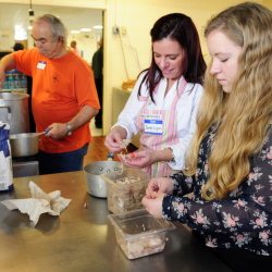 Ron Emery, left, stirs a gravy pot as Jamie Lynn Green and her daughter Savannah Green pick turkey meat off carving scraps for Emery to add to it Thursday before a community Thanksgiving dinner at Gardiner Area High School.