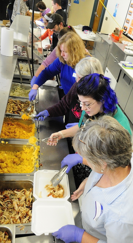 Volunteers serve up food into take-out boxes that were to be delivered at a community Thanksgiving dinner Thursday at Gardiner Area High School.