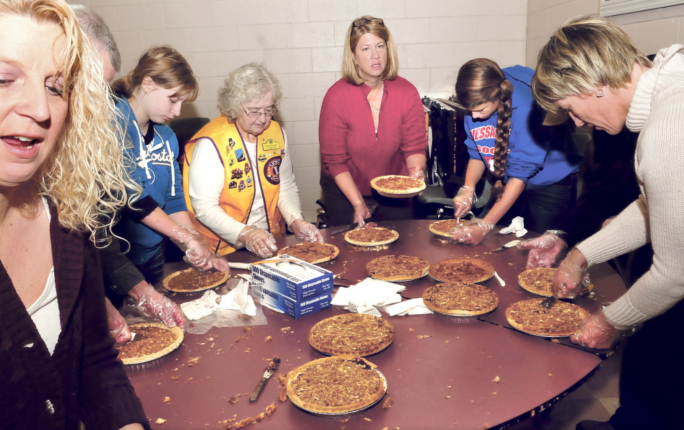 Volunteers slice and box dessert pies Thursday during the annual Thanksgiving dinner sponsored by Bud King and the Oakland Lions Club at Messalonskee High School in Oakland.