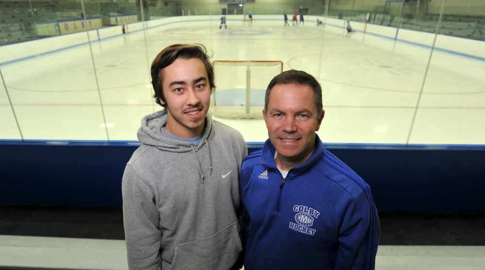 Staff photo by Michael G. Seamans   Colby College hockey coach Blaise MacDonald, right, stands with his son and Colby forward Cam MacDonald before a recent practice.