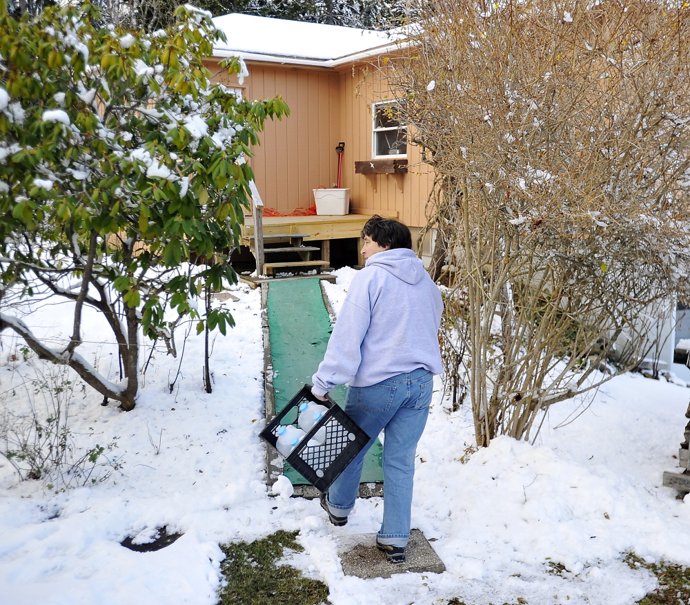 HARPSWELL, ME - NOVEMBER 28: Washburn Road resident Cynthia Forsyth carries  jugs of water from a nearby spring to help with the lack of electricity that usually run the pumps for her normal water supply. (Photo by Gordon Chibroski/Staff Photographer)