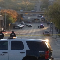 Police tape marks off the scene after a man opened fire on the Mexican Consulate, police headquarters and other downtown buildings early Friday in Austin, Texas. In the distance, police cars surround the suspect's vehicle parked near the Interstate 35 overpass.