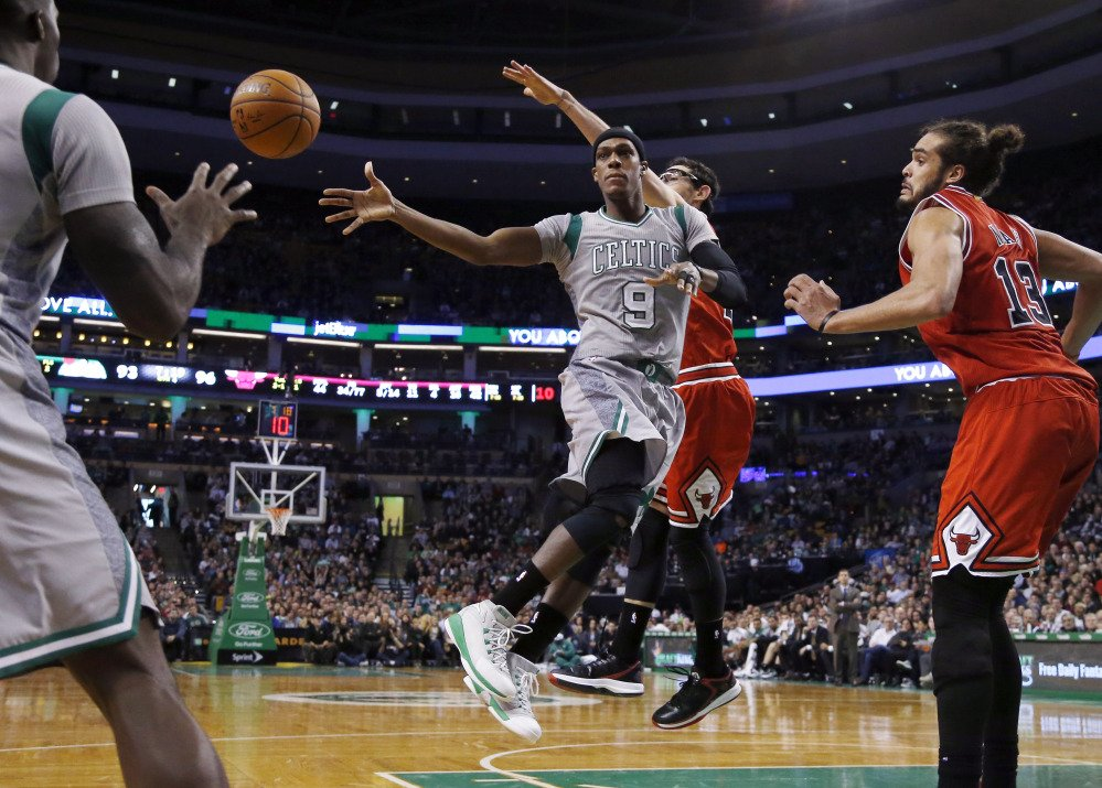 Boston Celtics guard Rajon Rondo (9) dishes to a teammate as he drives against Chicago Bulls guard Kirk Hinrich and center Joakim Noah (13) in the second half Friday in Boston. The Bulls won 109-102.