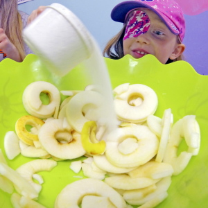 Caroline Netten, 5, of Augusta, takes part in a pie-making event Wednesday at the Children's Discovery Museum in Augusta. With help from volunteers, children made an apple pie that they could take home and bake.