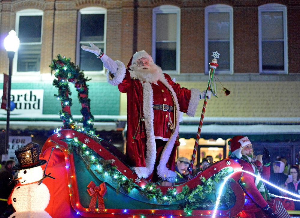 Santa Claus dances with his elves Friday evening on his float during the Parade of Lights in downtown Waterville.