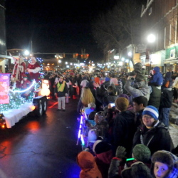 Santa Claus dances with his elves on his float Friday during the Parade of Lights in downtown Waterville.