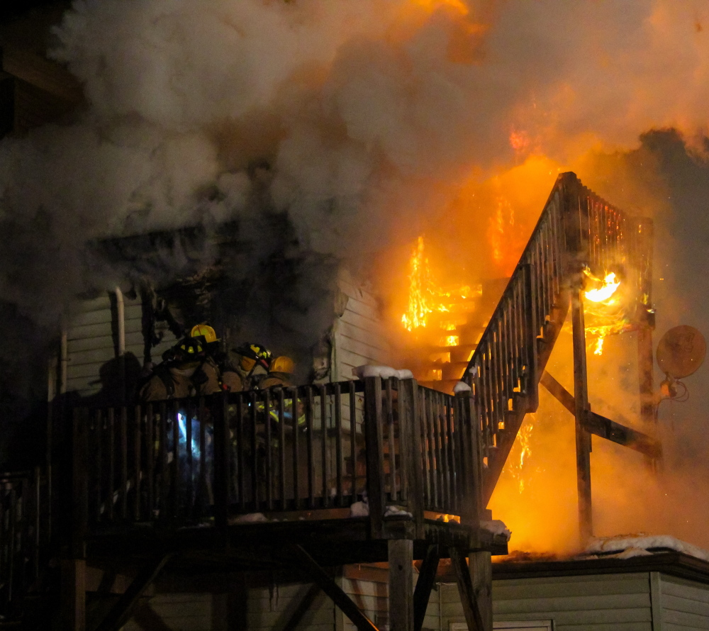 Firefighters make their way into a second-floor apartment during an apartment house fire in Berwick late Friday.