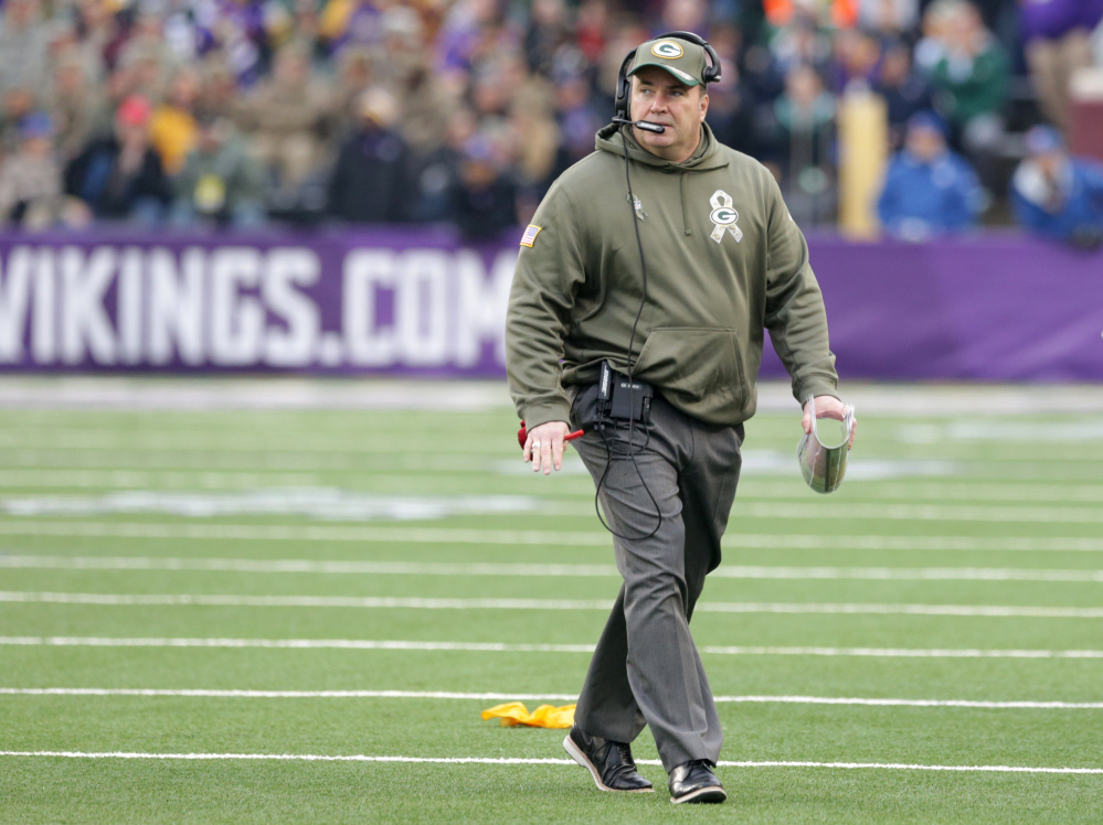 Green Bay Packers head coach Mike McCarthy walks on the field during the first half of an NFL football game against the Minnesota Vikings, Sunday, Nov. 23, 2014, in Minneapolis. (AP Photo/Jim Mone)