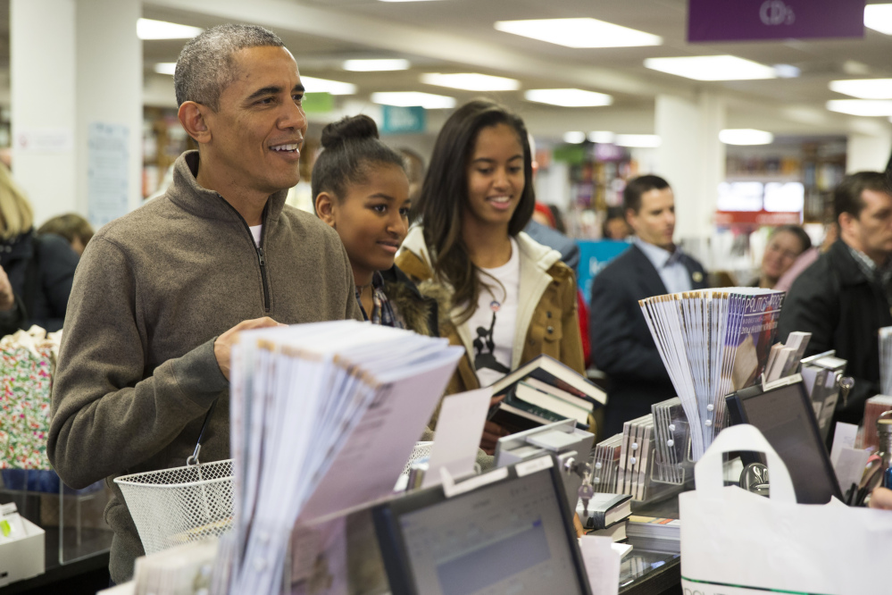 """The Associated Press President Barack Obama, left, shops with his daughters, Sasha, center, and Malia, at Politics and Prose bookstore for """"Small Business Saturday,"""" on Saturday in Washington."""