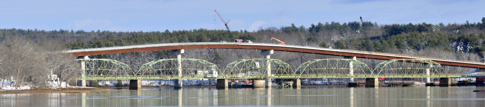 The old green metal bridge spanning the Kennebec River between Richmond and Dresden will be replaced by the new taller bridge with concrete supports following a Friday ceremony.