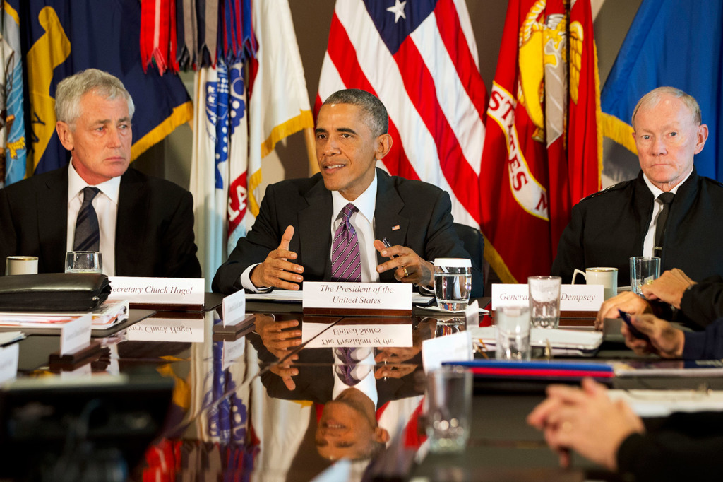 In this Oct. 8, 2014 file photo, President Barack Obama, flanked by Defense Secretary Chuck Hagel, left, and Joint Chiefs Chairman Gen. Martin Dempsey, speaks to the media at the conclusion of a meeting with senior military leadership, at the Pentagon. Defense Secretary Hagel is resigning from the Obama Cabinet Monday. The Associated Press