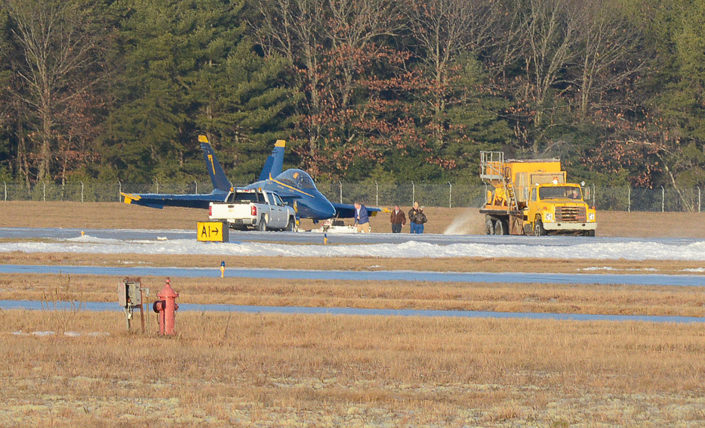 Ice melting product is spread by a crew after Blue Angels #7, flown by Capt. Jeff Kuss and Corrie Mayes, slid off the runway after landing at the Brunswick Executive Airport Thursday. John Patriquin/Staff Photographer