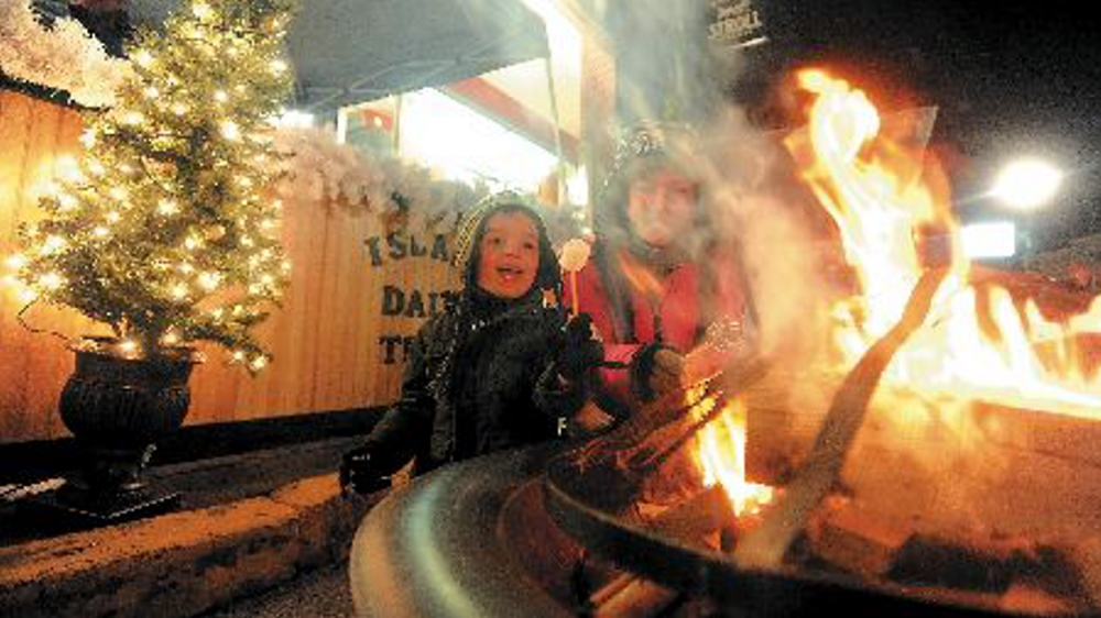 Christina Easler, right, and her son Gavyn, 4, toasted a marshmallow over an open fire on Water Street at the Parade of Lights on Water Street in downtown Skowhegan last December. The annual event returns this weekend, one of a number of events planned in the region as the holiday season moves into full swing.
