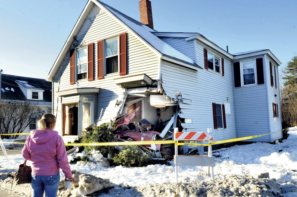 Shannon Thaller, who said she was a housekeeper for the owners of this house, surveys the damage left after a tractor trailer struck the building on Madison Avenue in Skowhegan on Tuesday. The building had a gaping hole in the corner. Thaller said she couldn't believe the damage and was glad no one was home when the incident occurred.