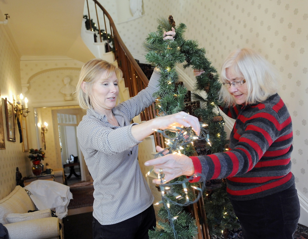 Debbie Sherman, right, takes holiday lights from Tammy Costigan on Tuesday while wrapping garland on the stairs of the Blaine House with other members of the Kennebec Valley Garden Club.