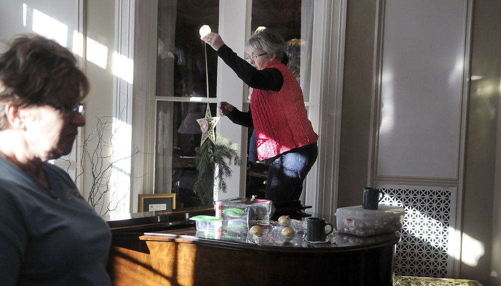 Shelly Hanson, right, and Pam Johnson decorate the Blaine House on Tuesday with other members of the Kennebec Valley Garden Club. The group chose a military theme this year.
