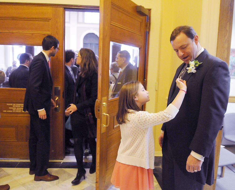 Elaina Eves, 9, adjusts the flowers on the jacket of her father, Speaker of the House Mark Eves, D-North Berwick, before he entered the House chamber to vote for constitutional officers in Augusta on Wednesday.