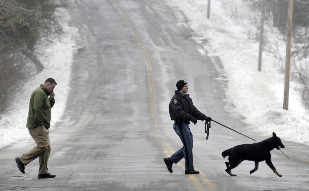 State Trooper G.J. Neagle accompanies his tracking dog with Augusta Police Dept Detective Chris Blodgett while searching Wednesday for a person reported to be in the woods between Farrington Elementary School and Cony High School in Augusta.  Both school were locked down for about an hour while police searched the woods. Nobody was found, according to police. Staff photo by Andy Molloy
