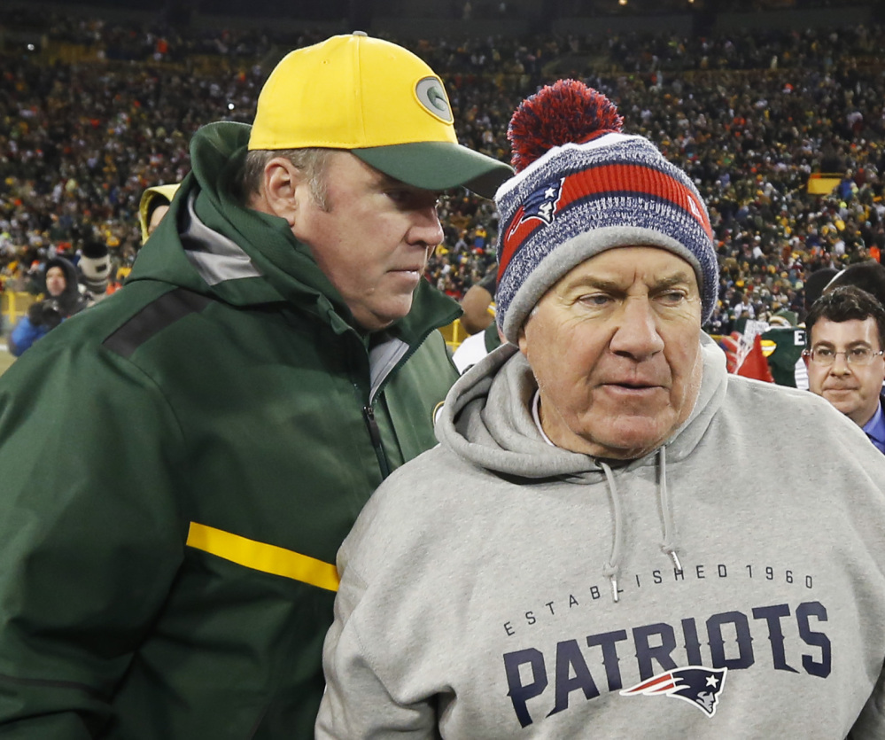 Green Bay Packers head coach Mike McCarthy talks to New England Patriots head coach Bill Belichick after Sunday's game in in Green Bay, Wis. Belichick won't need a winter hat this week, as the Patriots play the San Diego Chargers.