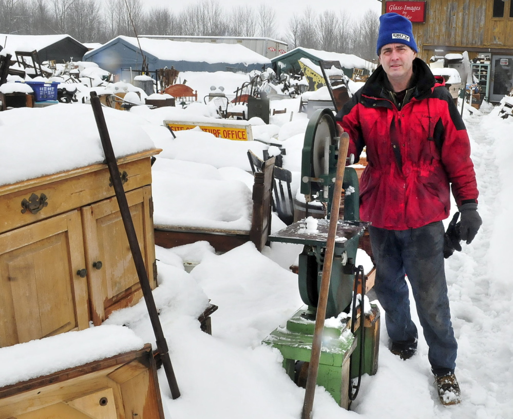 Robert Dale, owner of Maine 201 Antiques, stands in the middle of a sprawling collection of household items, farm equipment, glass and metal items in Fairfield in March. Dale has been ordered to clean up the property, and a judge this week ordered him to pay the town $28,369. He'll be in court again in January.
