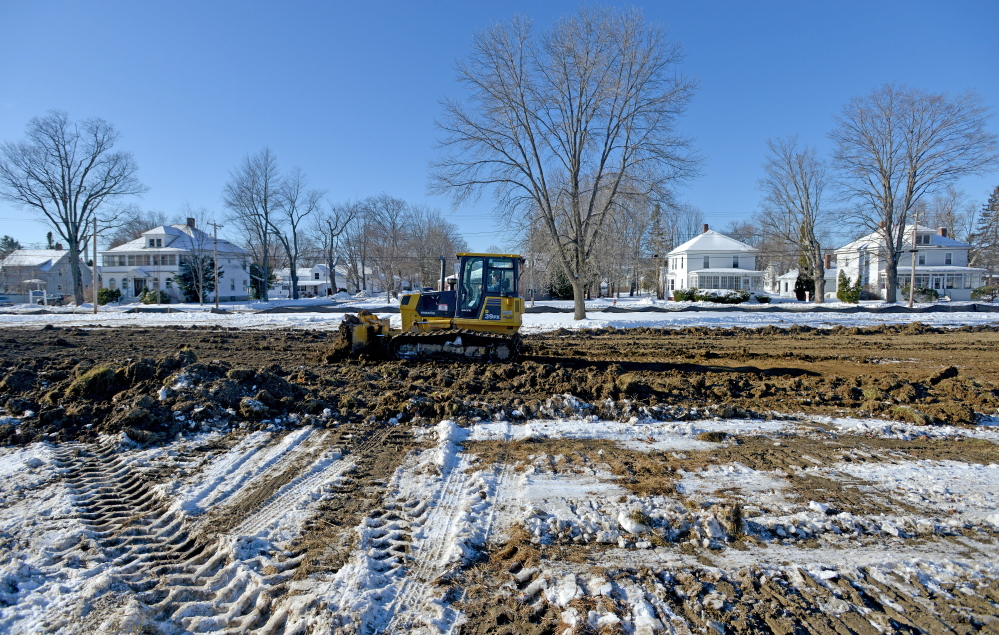 Ronald Peters levels out the site of a new public skating rink Thursday on Weston Avenue in Madison.