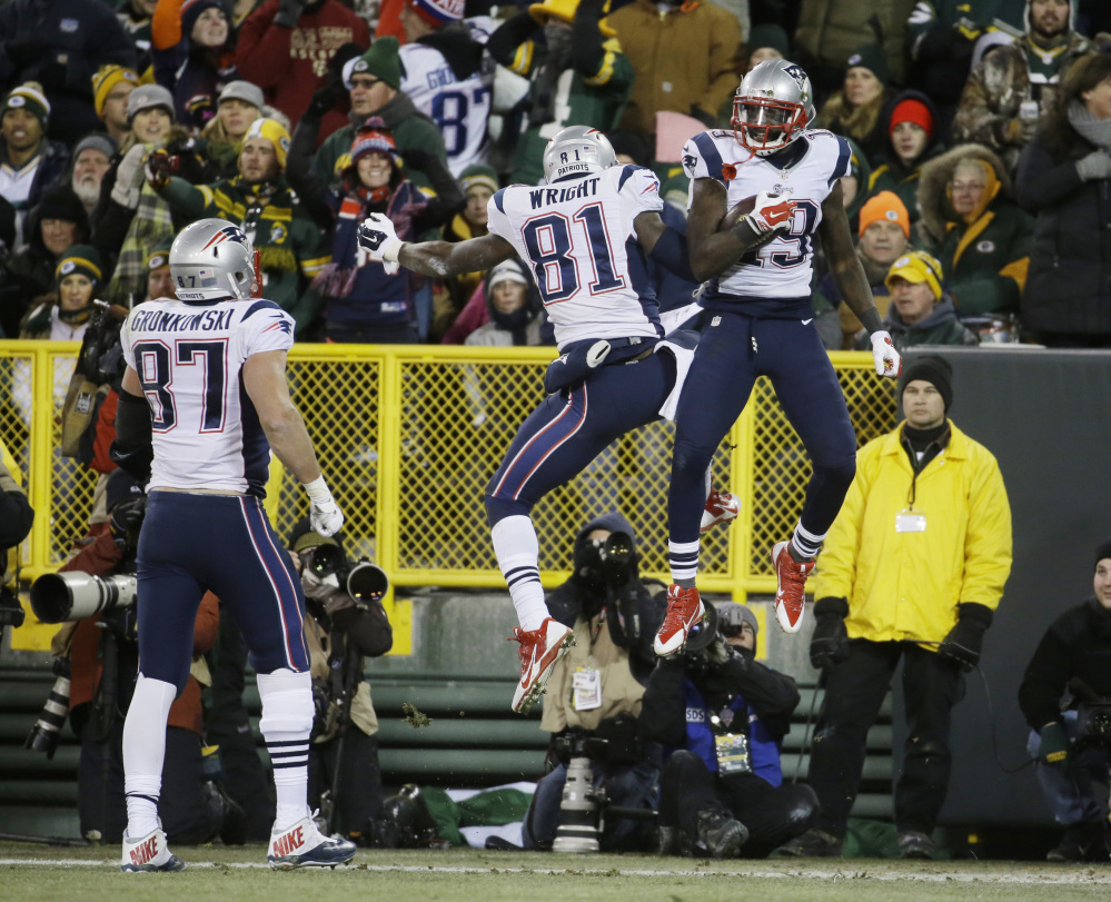 New England Patriots' Rob Gronkowski (87) watches as Brandon LaFell (19) celebrates his touchdown catch with Timothy Wright (81) during the second half Sunday against the Green Bay Packers in Green Bay, Wis.