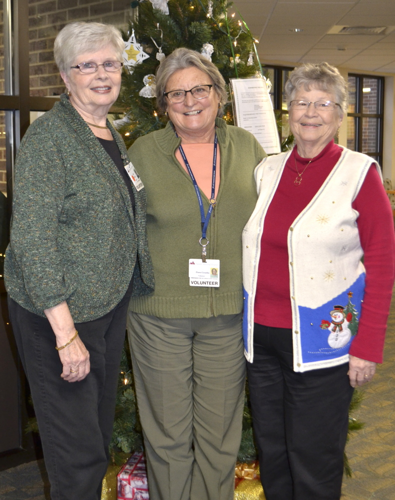 From left Auxiliary members Jean Rand, Dawn Girardin and Mary Harris in front of the Remembrance Tree.