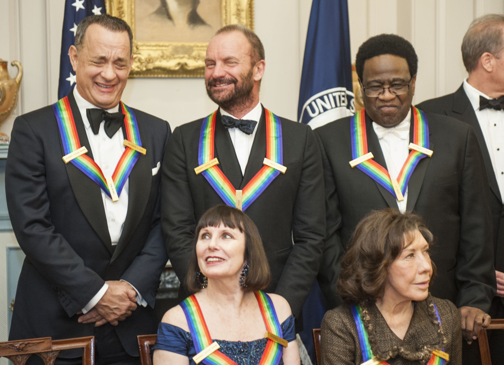 2014 Kennedy Center Honorees Tom Hanks, and Sting share a laugh as they gather with Patricia McBride, front left,  Lily Tomlin, front right, and Al Green, right, following the State Department Dinner for the Kennedy Center Honors on Saturday in Washington.