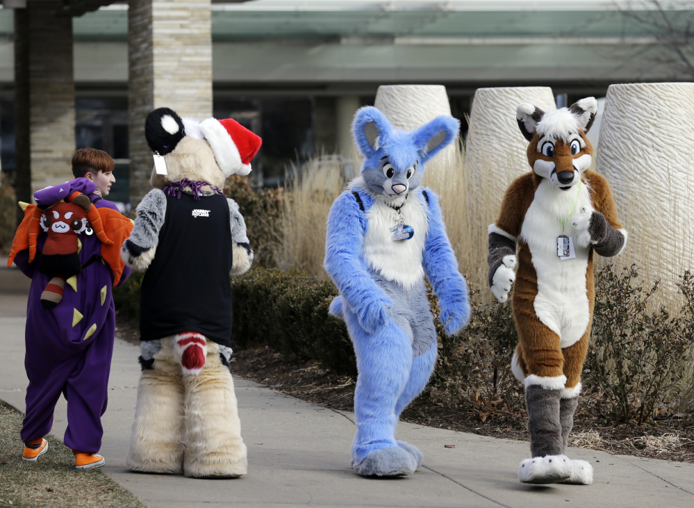 Frederic Cesbron, right and Maxim Durand, walk on the street outside the Hyatt Regency O'Hare hotel on Sunday in Rosemont, Ill. Thousands of people were evacuated after a chlorine gas leak at the hotel hosting the 2014 Midwest FurFest convention.