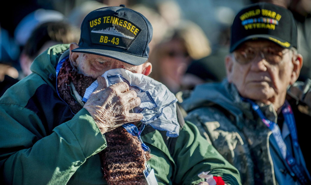 """U.S. Navy veteran Robert MacLennan, 92, of Sanford, Va, wipes a tear after being presented with a flower during a Pearl Harbor remembrance service in Washington. """"In a way, I feel honored,"""" he said, """"but in another way, it gives you nightmares."""""""