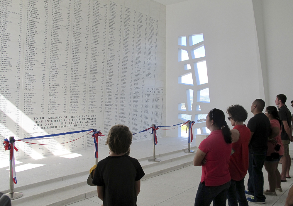 This Nov. 21, 2014 photo shows visitors looking at a wall inscribed with the names of the USS Arizona's fallen at a memorial for the sunken battleship in Pearl Harbor, Hawaii.