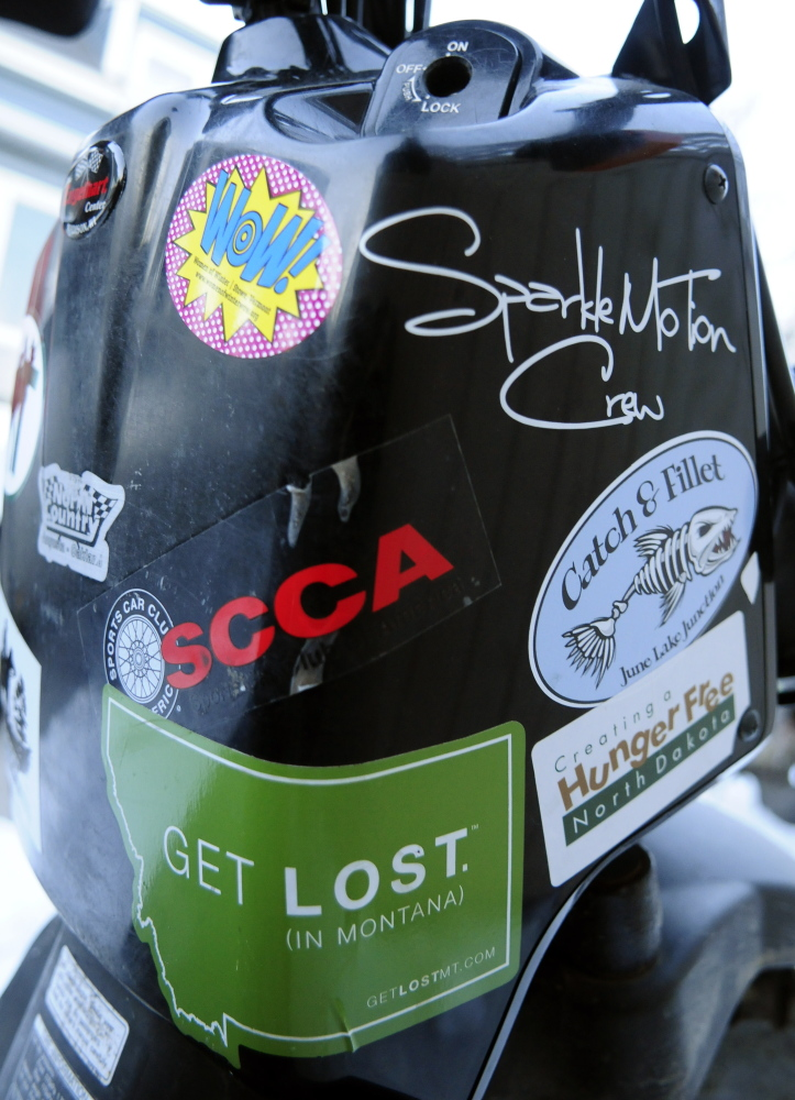 Stickers collected during a cross-country trip cover Dan Emery's Honda scooter Thursday in Augusta.