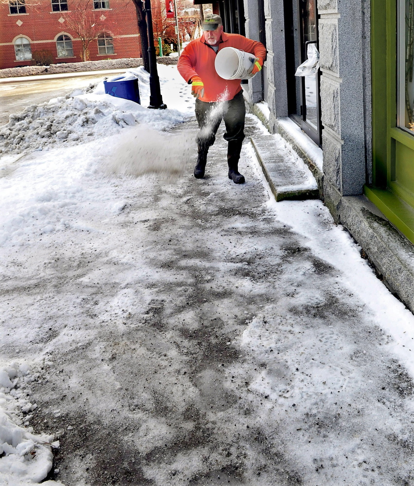 """Bruce Heath of KB Property Care spreads salt on icy sidewalks in Waterville Sunday. He may be out a few more times in the next few days as a storm system is expected to bring a mix of rain and snow to central Maine for a few days. """"I've been quite busy lately,"""" Heath said."""