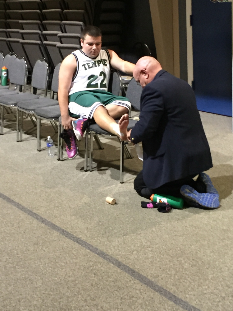 Temple boys basketball coach Tom Simmons tapes an ankle of junior Tristan Richards before a game Monday against Greater Portland Christian.