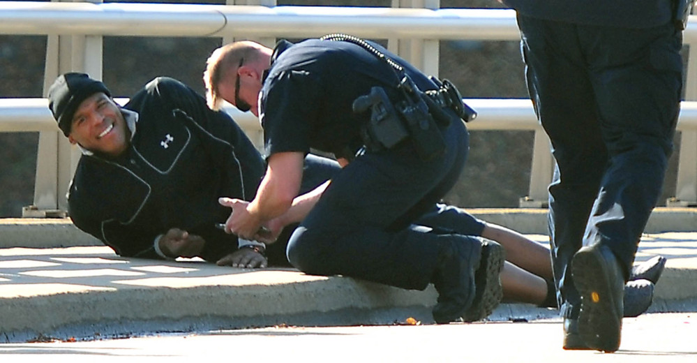 A Charlotte-Mecklenburg police officer tends to Carolina Panthers NFL football quarterback Cam Newton following a two-vehicle crash not far from the team's stadium in Charlotte, N.C., Tuesday.