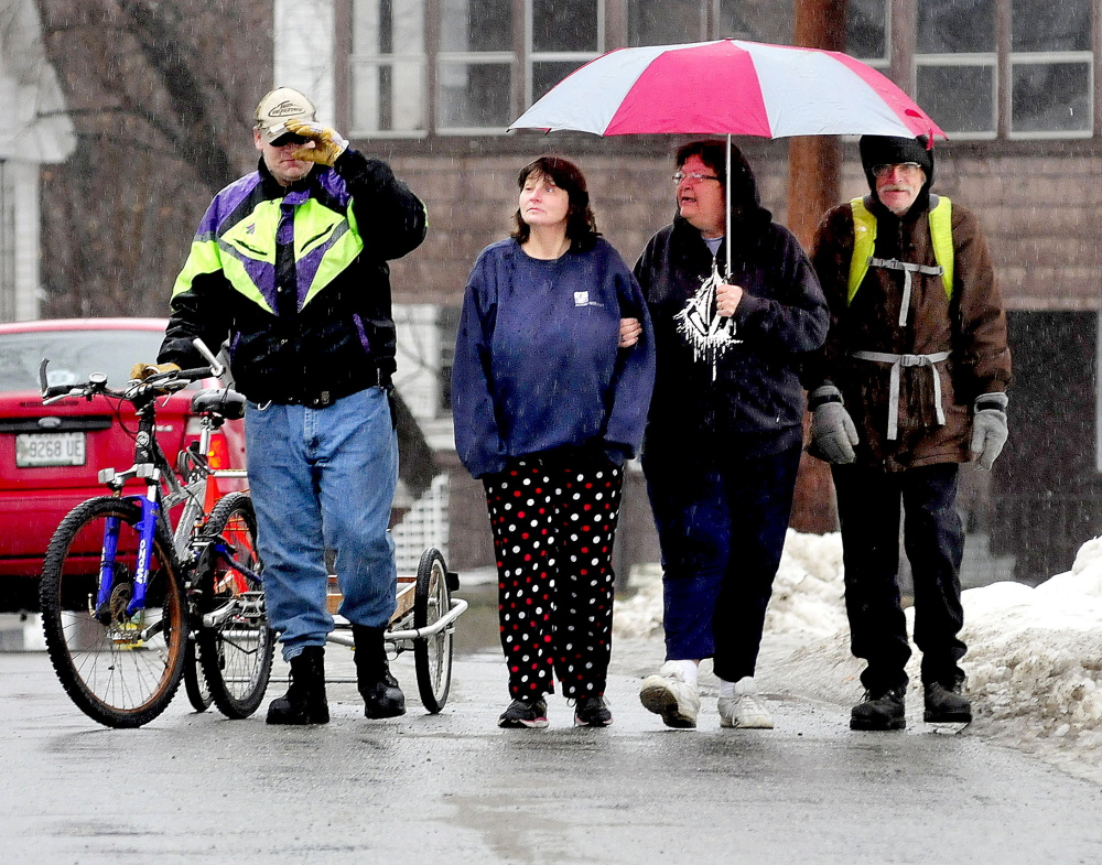 Doug Whitney, with bike, and Lisa Douglass, and Betsy and Francis Dittman share an umbrella in the rain in Waterville on Wednesday.