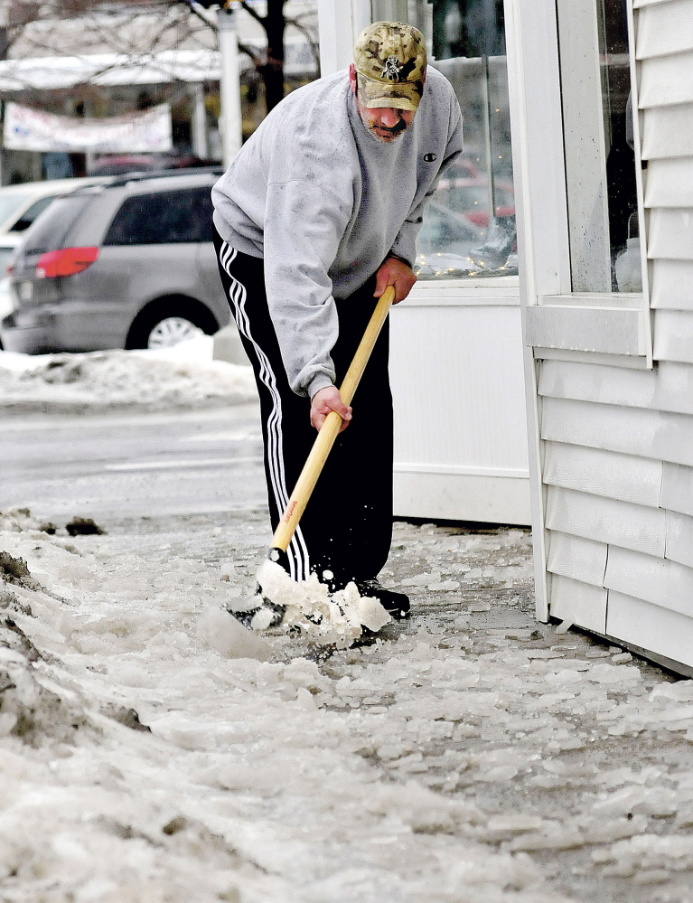 Lee Poulin uses a chisel to chop ice covering sidewalks in Waterville on Wednesday.