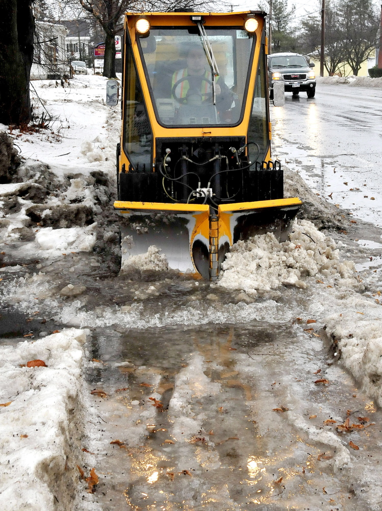 Aaron Poulin of the Fairfield Public Works Department plows snow, ice and water on sidewalks in Fairfield on Wednesday.