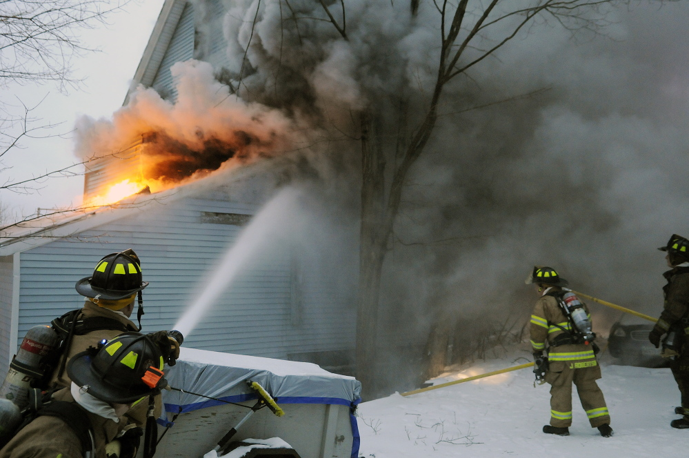 Firefighters battle smoke and flames Tuesday at a blaze on State Street in Augusta.